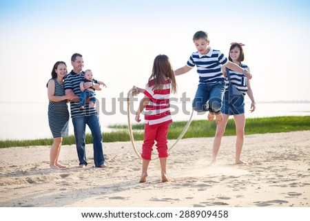 Summer family vacation - boy playing with skipping rope on the beach - stock photo