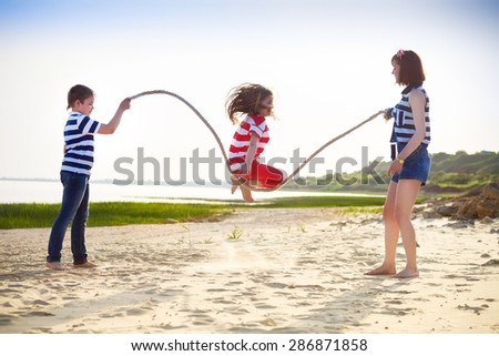 Summer family vacation - girl playing with skipping rope on the beach - stock photo