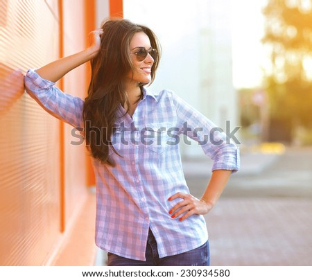 Summer, fashion and people concept - beautiful smiling woman in sunglasses posing against colorful wall, street fashion - stock photo