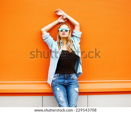Summer, fashion and people concept - bright stylish pretty blonde posing in sunglasses against colorful wall background in the city, copy space, street fashion photo - stock photo