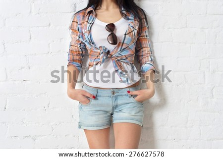 Summer, fashion and people concept - bright stylish pretty brunette in shirt posing in sunglasses against colorful wall background in the city, street fashion photo. - stock photo