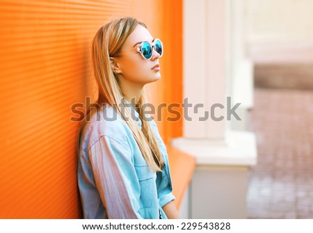 Summer, fashion and people concept - lifestyle portrait stylish pretty woman in sunglasses against colorful wall in city, street fashion - stock photo