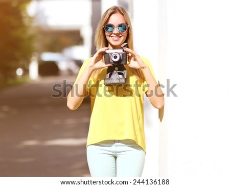 Summer, fashion and people concept - sunny portrait smiling pretty woman with old retro vintage camera having fun outdoors - stock photo