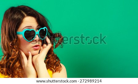 Summer fashion eyes protection concept. Closeup girl long curly hair in heart shaped sunglasses on green vivid color background