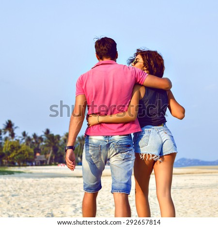 Summer fashion image of stylish hipster couple posing at lonely exotic beautiful beach, hugs and kisses, joy , enjoy their vacation, bright trendy clothes, sunny colors, positive mood. - stock photo