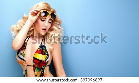 Summer fashion photo of stylish beautiful blonde woman in bikini. Blue background.