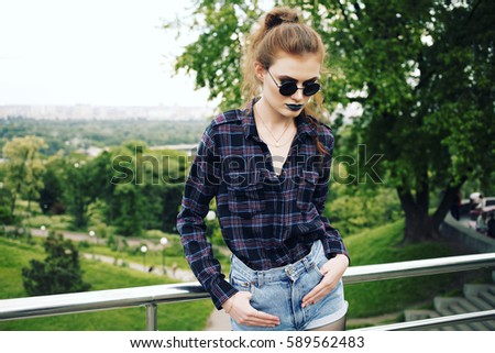 Summer fashion portrait of beautiful young skinny hipster girl in a plaid shirt and jeans shorts in stylish sunglasses and blue lipstick. Outdoors, lifestyle