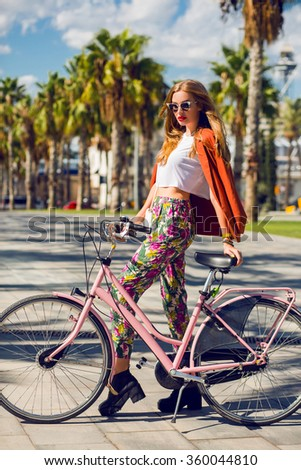 Summer fashion portrait of pretty blonde woman  posing with   pastel pink cruiser bicycle in Barcelona. Trendy street style,  breeches with print, orange  jacket,  shirt top. Palms background.