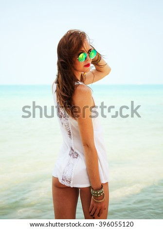Summer fashion portrait of stunning woman with tanned fit sexy body, wearing white lacy t-shirt and stylish round sunglasses, posing at tropical island beach with clear blue water. - stock photo