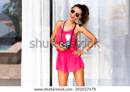 Summer fashion portrait of young sexy woman posing smiling and having fun, wearing neon stylish jumpsuit and sunglasses, holding funny retro camera. - stock photo
