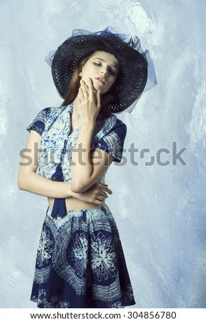 summer fashion shoot of cute female in romantic pose with hat and elegant skirt and top, long hair natural make-up  - stock photo