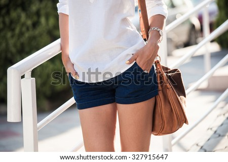 summer fashion woman in white shirt and shorts  stand by  fence, outdoor shot,  summer day, closeup