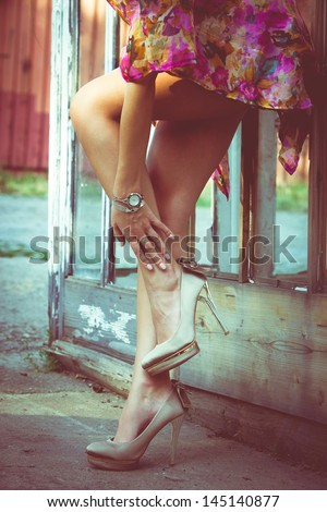 summer fashion woman with long slim legs in high heel shoes against old door with glass  outdoor shot retro colors
