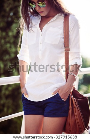 summer fashion woman with sunglasses in white shirt and shorts  stand by  fence, outdoor shot,  summer day - stock photo