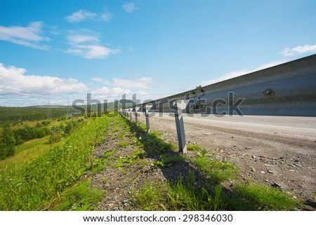 Summer field of grass on a sunny day and road - stock photo