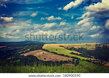 Summer field under cloudy sky in mountains during morning - stock photo