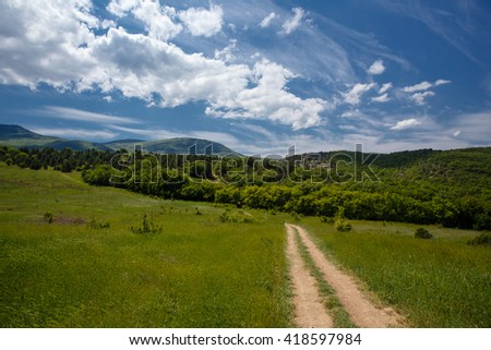 Summer field with road and clouds in blue sky. Beautiful summer field at sunny day - stock photo