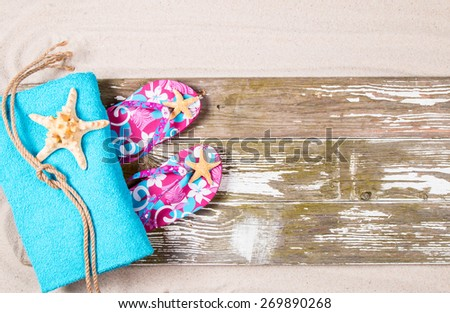 Summer flip-flop and towel   on a wooden boards against sandy background. - stock photo