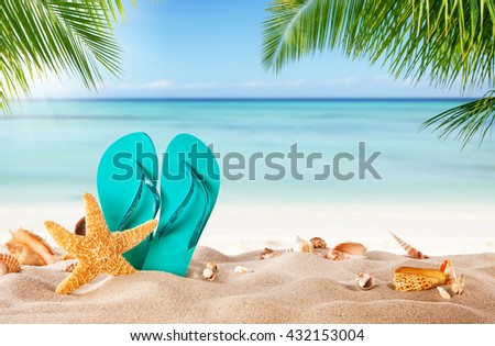 Summer flipflop on sandy beach, blur sea on background. Summer exotic relaxation concept - stock photo