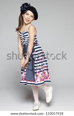 Summer flirty little girl. Full length of little girl wearing sundress in marine style over gray background. - stock photo