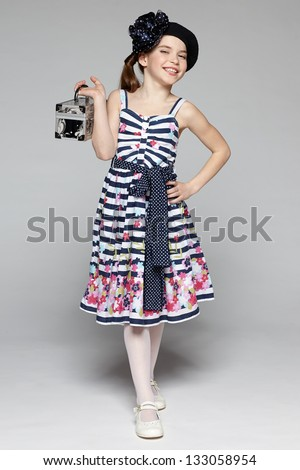 Summer flirty little girl walking with a box. Full length of little girl wearing sundress in marine style over gray background. - stock photo