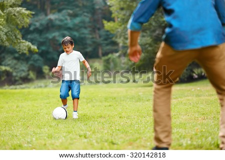 Summer football. Dad and son playing soccer on a green grass in the park. Family weekend.