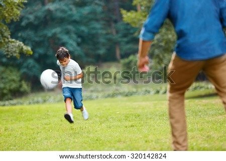 Summer football. Dad and son playing soccer on a green grass in the park. Family weekend. - stock photo