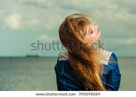 Summer freedom happiness concept. Girl long blonde hair enjoying summer breeze by seaside - stock photo