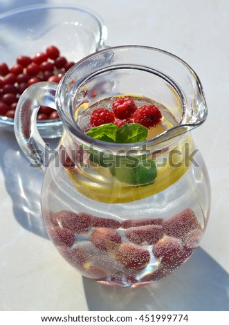 Summer fresh fruit flavored infused water mix of lemon, raspberry, Japanese silverberry and mint. Detox homemade cocktail in glass jug. Healthy diet plan. - stock photo