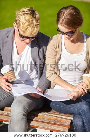 summer, friendship, education and teenage concept - f happy student couple with notebook learning and drinking coffee at campus - stock photo