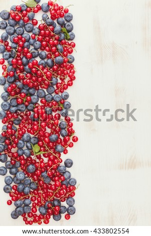 Summer fruit assortment. Beautiful red currant and blueberry on rustic table with space for text . Overhead view - stock photo