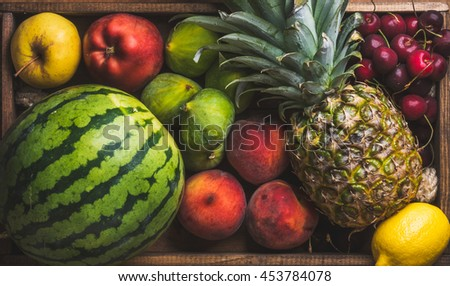 Summer fruit variety on wooden background, top view. Watermelon, pineapple, lemon, figs, peach, sweet cherry and apple
