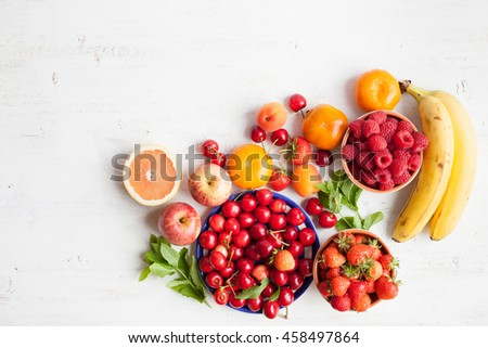 Summer fruits and berries (strawberries, cherries, raspberries, oranges, grapes, persimmon) on a white table, space for text, selective focus - stock photo