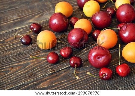 summer fruits on dark wooden table.Plum, apricot, cherry on vintage wooden background - stock photo