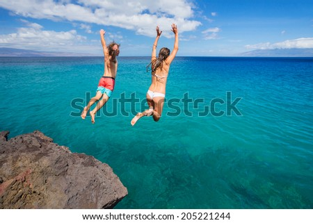 Summer fun, Friends cliff jumping into the ocean.  - stock photo