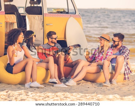 Summer fun. Group of joyful young people drinking beer and playing guitar while sitting on the beach near their retro minivan - stock photo