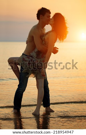 Summer fun holiday on beach background. A loving young couple hugging and kissing on the beach at sunset. Two lovers, man and woman near the water. Summer  scene in love  sunset sky