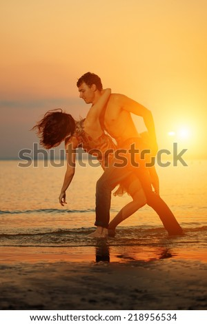 Summer fun holiday on beach background. Couple in love in beach party. Summer scene about dance,  dancing, sunset sky - stock photo