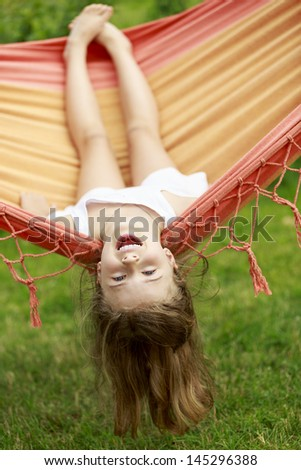 Summer fun in the garden - lovely girl playing in hammock - stock photo