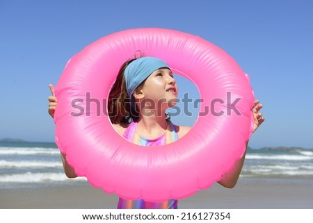 summer fun portrait: child with inflatable swimming ring at the beach - stock photo
