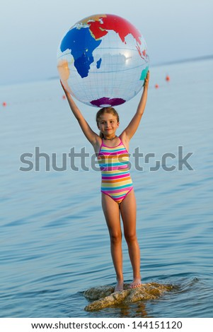 Summer game, young girl playing in the sea - travel concept - stock photo