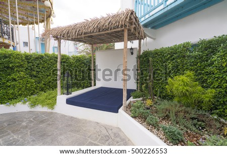 Summer garden gazebo or tropical hut and sofa bed for relaxation.