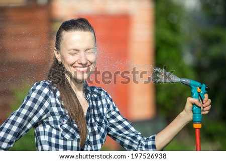 Summer garden, watering - beautiful woman watering lawn with garden hose in the garden - stock photo