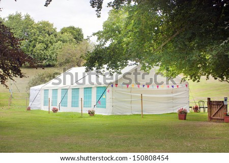 summer garden with a marquee tent on the grass - stock photo
