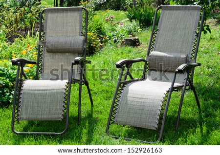Summer garden with flowers and sun loungers