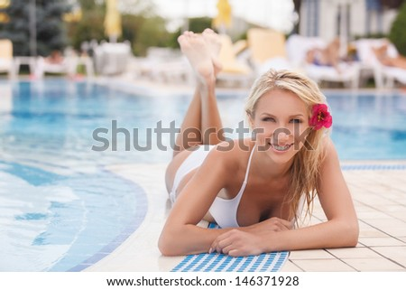 Summer girl. Attractive young women in bikini lying on the poolside and smiling at camera - stock photo