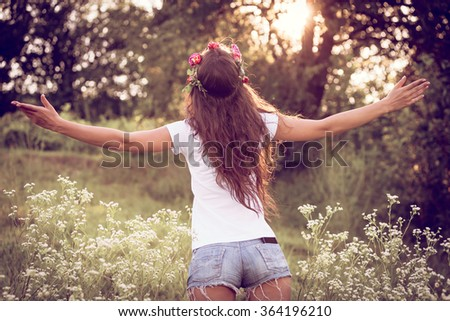 summer girl in jeans shorts and white t-shirt with open arms welcome nature, back shot, outdoor in field at sunset - stock photo