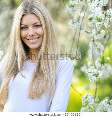 Summer girl portrait. Beautiful blonde woman smiling on sunny summer or spring day outside on a meadow - stock photo