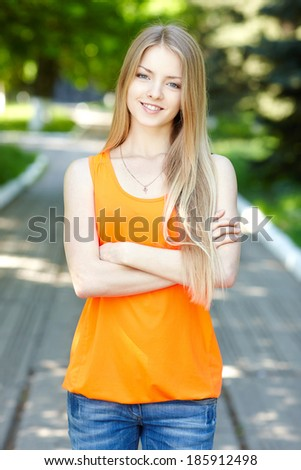 Summer girl portrait.  Casual woman standing with folded hands smiling happy on sunny summer or spring day outside in park. Pretty young woman outdoors. - stock photo