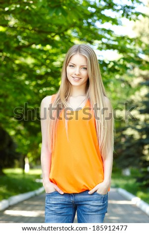 Summer girl portrait.  Casual woman standing with hands in pockets smiling happy on sunny summer or spring day outside in park. Pretty young woman outdoors.